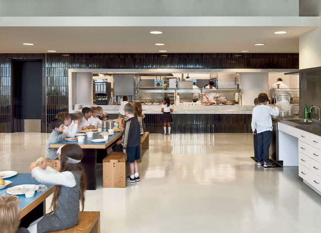 Encased in deep- green-glazed tile, the food-service station is open on two sides to dish up the day's specials on marble counters to both upper- and lower-school children. Small teaching kitchens al