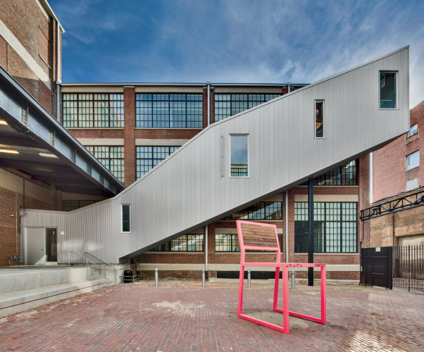 The architects erected two external corrugated-aluminum stairwells along facing walls in the courtyard.