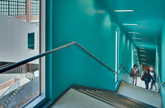 A vibrant turquoise packs a punch, within one of two external corrugated-aluminum stairwells the architects installed along facing walls in the courtyard.