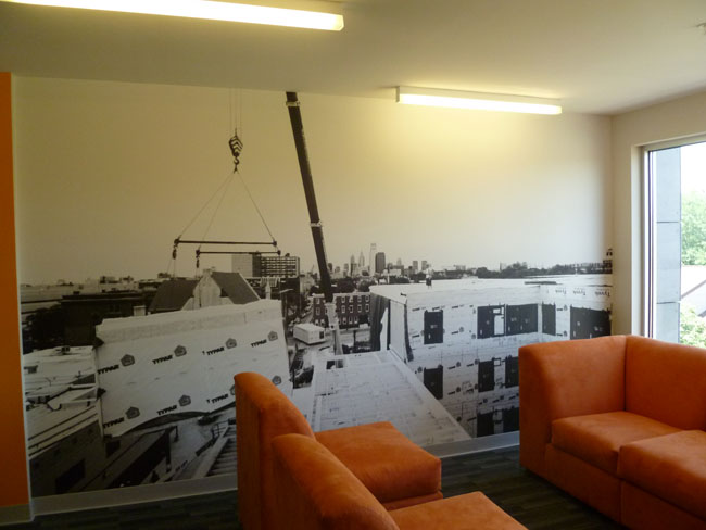 A photo mural in one of the building's lounge spaces shows its modular construction.