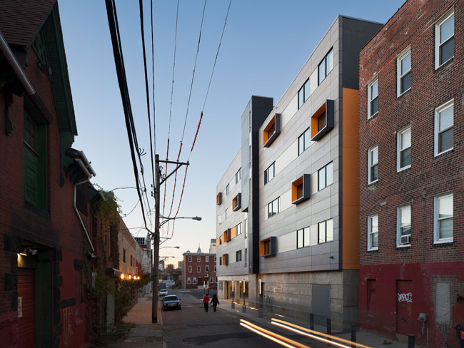 The project stands across from a low-rise public housing project and is flanked by brick buildings.