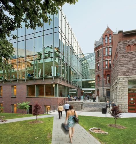 An academic entrance leads from a landscaped path into an atrium that joins new and old construction.