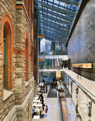 The atrium is defined on one side by the historic building's colorful and highly textured masonry and a sleek stone-clad wall on the other. The route to the new hall from the main entry and box office
