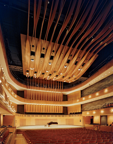 A canopy of ribbonlike laminated oak strips twisted in jigs provides the room's defining element and helps conceal speakers, lighting, and other equipment. It serves as the backdrop for the chorus, th