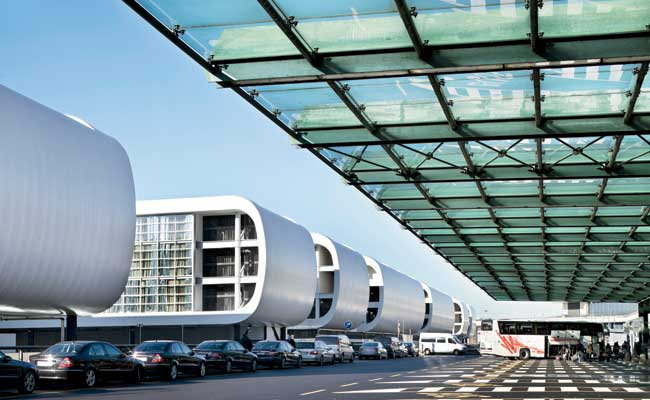 The hotel faces Terminal 1 with a taut fiberglass skin. The architects maintained this clean continuum on the roof by inserting the mechanicals within the curves of the modules.