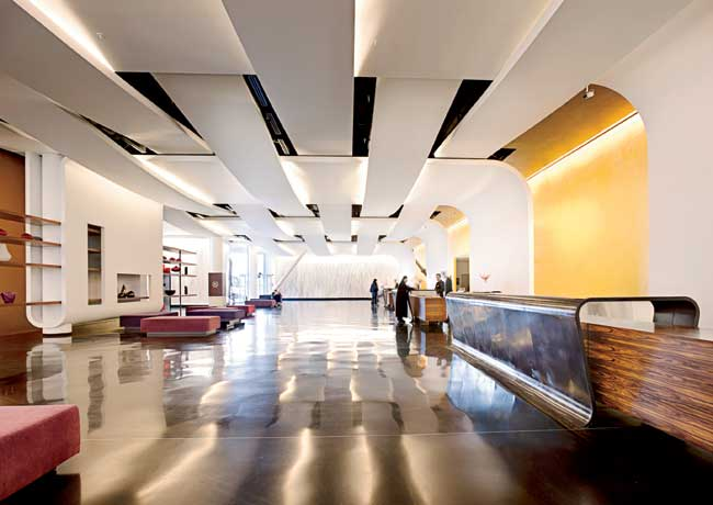 The architects carried their bold gestures for the exterior into reception. Ceilings and wall bands undulate, and dramatic composite terrazzo desks flow up from the floor with mirrored sides that emph