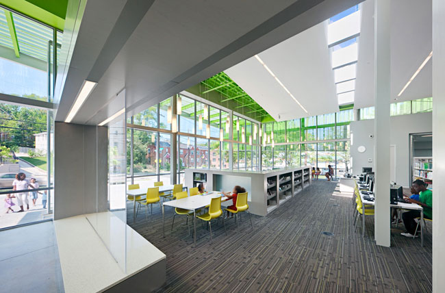 The ample amount of glass curtain walls and skylights limits overdependence on electric lighting. Glare is cut by the green perforated metal screen.