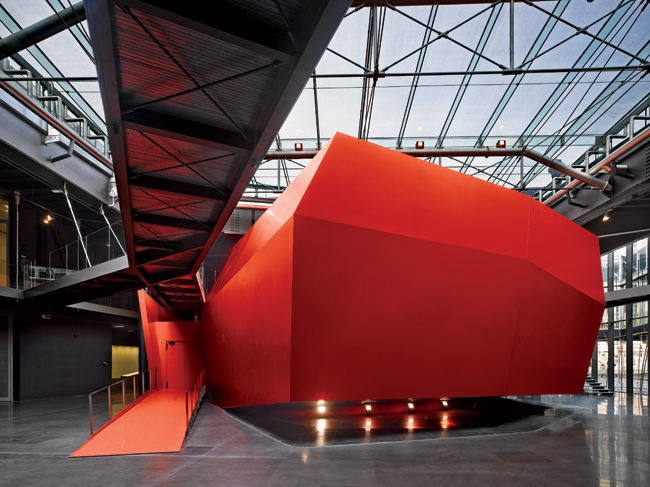 A bright red faceted polygon houses an auditorium and serves as the vibrant heart of the 108,000-square-foot expansion of the museum.