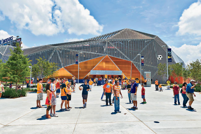 Splashes of bright orange, the color of the Houston Dynamo, erupt in polycarbonate patches from the  mesh-covered faceted exterior on the soccer stadium's entrances.