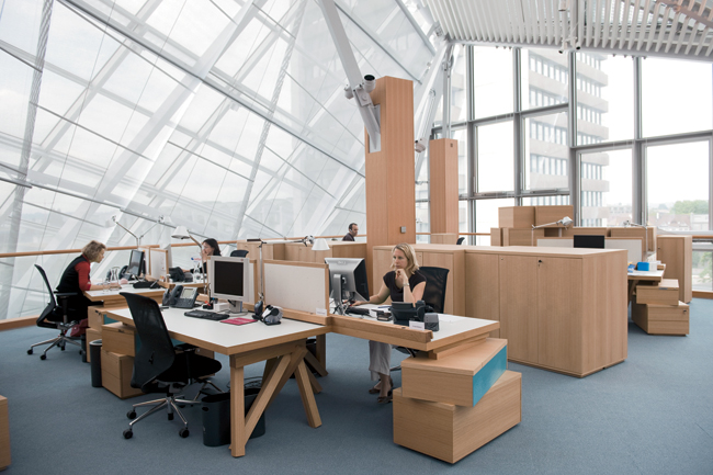 Employees sitting at workstations designed by Frank Gehry are protected from the sun's glare by a sophisticated system of saillike shades, controlled by daylight sensors. Artemide Tolomeo desk l