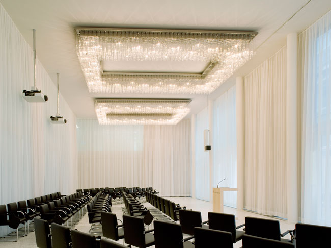 Krischanitz collaborated with Licht Kunst Licht principal Andreas Schulz to create glittering chandeliers for the lab building's refined auditorium. Comprising clusters of crystalline glass cylinders