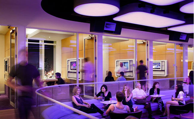 The Rockwell Group'designed Yotel has a daytime meeting room that transforms into a bar at night. To accommodate both uses, ceiling panels backlit with color-changing LEDs can fill the space with eith