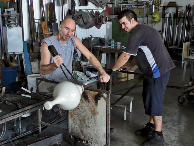 Glassblowers near Murano, Italy, work on early prototypes of the lamps.