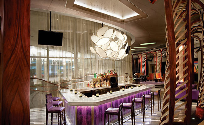 The Bar Vdara, by Therese Viserius Design, is separated from the hotel's lobby by perimeter rose wood screens that echo the curve of the building footprint.