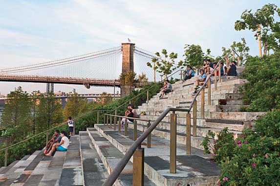 A wide stair of salvaged, rough-hewn granite blocks steps down a slope like raked theater seats providing views of the river, two bridges, and Manhattan.