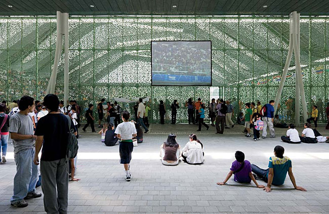 Fans watch a sporting event projected onto a screen in the interstitial space outside the arenas. They also observe it firsthand through the punched metal facades that veil the structure and emphasize
