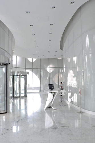 In the lobby, the architects designed the powder-coated aluminum reception desk to echo the curve of the walls and blend in with the luminescent white marble floors.