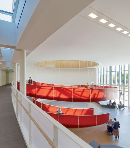 A 56-foot-diameter helical ramp off the lobby serves as a social hub for visitors and people working in the building. Wide enough for two wheelchairs to descend together, so people can continue conver
