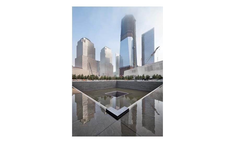 Water around and in the memorial pools reflects the skyline of Lower Manhattan without the Twin Towers.