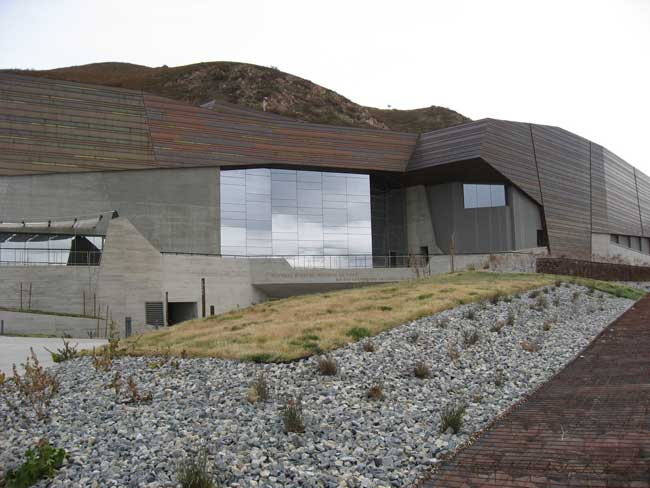 The glazing, which has a frit and a low-e coating, mirrors the sky and the museum's environs.