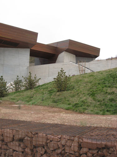 The museum is configured as a three-bar form that steps up with the terrain.