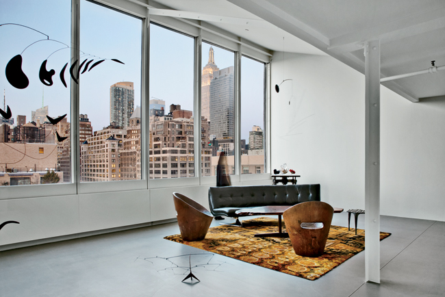 Large new windows orient a room to north light and views and provide a dramatic setting for a table by George Nakashima, wood chairs by Zanine Caldas, and a couch by Vladimir Kagan. Goto designed the
