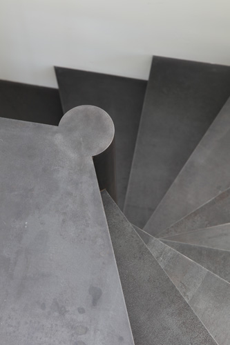A new stair to a private office is made of raw steel and is the only new element that is not white or off-white.