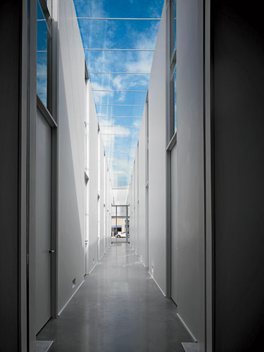 The soaring, double-loaded corridor is animated by a crystal-clear linear skylight and shadows cast from above.