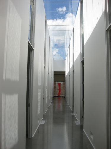 A red painted steel sculpture by Nigel Hall is visible at the end of the long, skylit corridor.