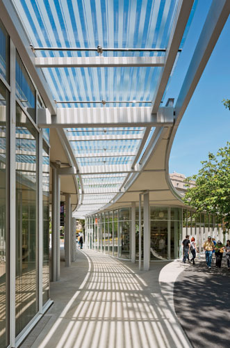 A fritted-glass canopy protects a breezeway from the full effects of the sun, providing a shaded path between the garden shop (right in photo) and the main building (left in photo).
