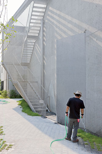 The metal exterior stair is the one place where visitors can occupy the space between the mesh and the building.