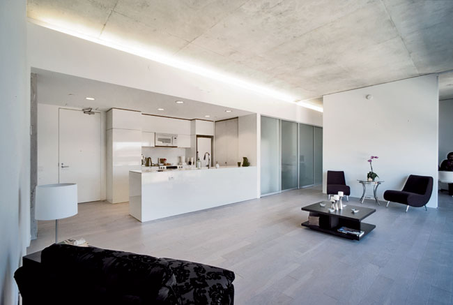 The exposed-concrete ceilings continue in the individual units. Services and mechanicals line one wall, freeing up the rest of the apartments for loftlike living. Partitions with sliding doors separat
