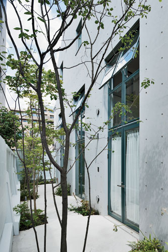 Keiko + Manabu infused the building with interior-design techniqes: A garden walk adds charm to the rental apartments.