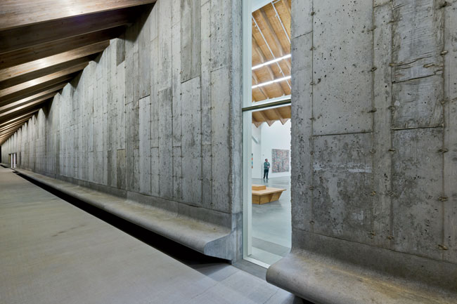 Outside, the concrete facade slopes out into a bench, allowing visitors to contemplate the landscape under the Parrish's deep eaves.
