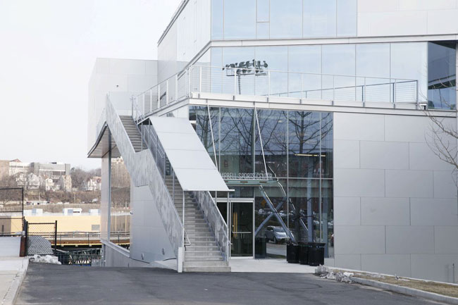 The main entrance is flanked by another exterior stair, which leads to a terrace above.
