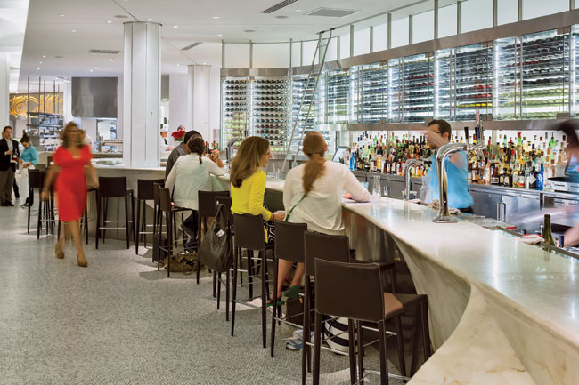 The serpentine marble counter swerves to include an elongated wine bar.