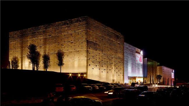 Nighttime lighting gives a new concrete block containing a multiplex theater (left in photo) the look of a Phoenician or Roman wall.