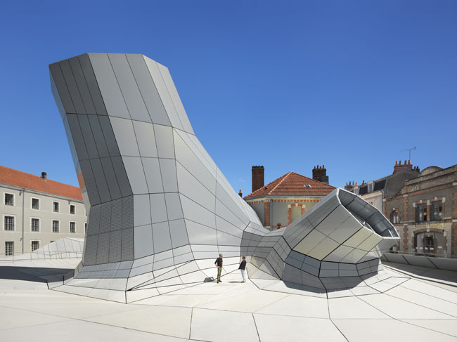 The digitally computed, faceted form with irregular angles is covered by a rainscreen of aluminum panels, and below them, precast concrete panels. Brendan MacFarland (left) talks to photographer Rolan
