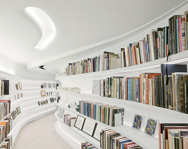 The collector's books are arranged on shelves along the back side of the major gallery wall, which is suspended from the existing ceiling's structure. The sinuously meandering space separates the gall