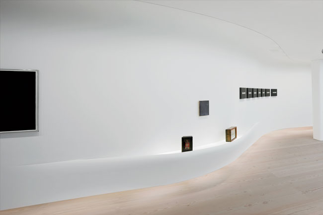 On the side of the suspended wall facing the gallery, halogen fixtures for the cove lighting and fluorescent lighting for its underside accentuate the ethereal quality of this setting.