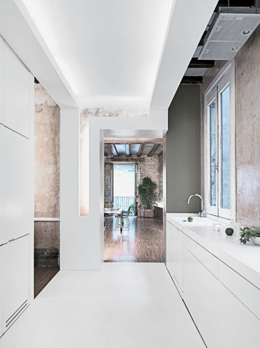 Softly illuminated cove lighting lines the perimeters of the walls and ceilings throughout the old and new spaces in the apartment, uniting them visually and imparting the illusion of an endless horiz