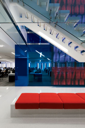 A vibrant blue tempered-glass wall provides a buffer between the open offices and the horizontal and vertical 'connector' near the building core.