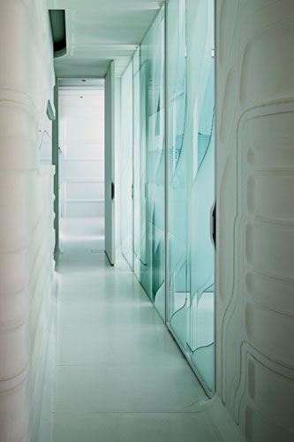 The etched-glass doors and walls of the patient examination rooms admit daylight into the windowless interior corridor.