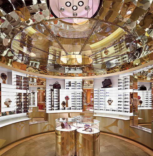 A whimsical circular boutique in the accessories area of the ground floor features numerous sunglasses displays reflected in a palpitating, dichroic-glass ceiling.