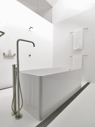 A top-lit bathroom on the second floor is lined in  white solid surfacing to emphasize its clarity and purity.