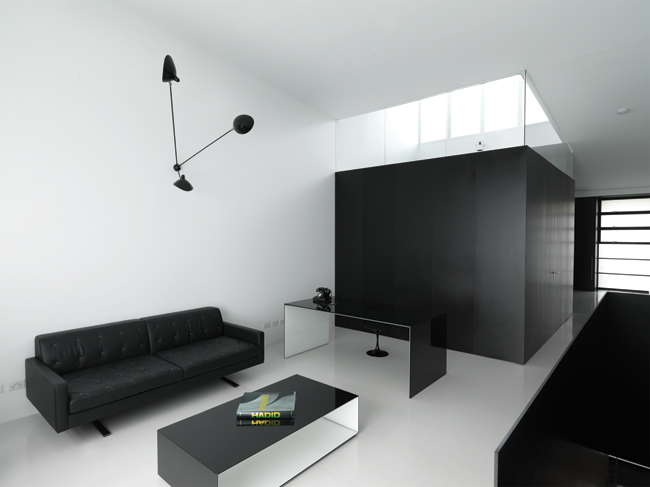 A black anodized aluminum box encloses the upper-level bathroom, which divides the sitting room from the bedroom. The floor is surfaced in white rubber. The rectilinearity of the laminated glass desk