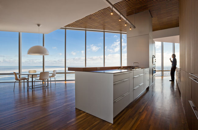 The architects hid a structural column in the kitchen by wrapping it with cabinets and opened views from the counter to the lake.