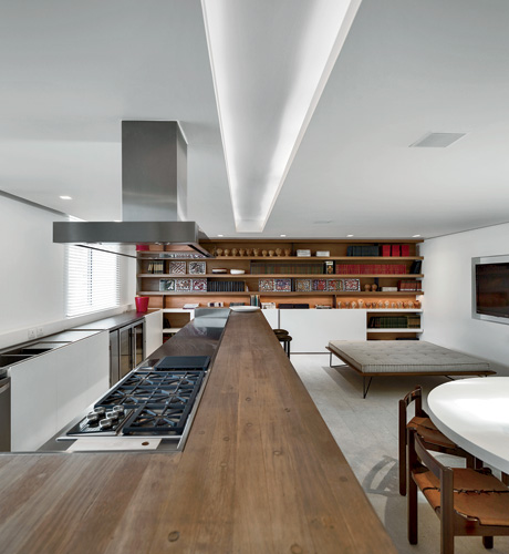 On the opposite side of the main level is the kitchen and dining area. Here, continuous planes for wood shelves and counters and limestone floors offer a natural counterpoint to the smoke-finished