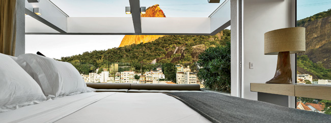 The master bedroom on the top floor faces southeast toward Sugar Loaf Mountain, and glass partitions between the bedroom and master bathroom bring the views and daylight into the interior. Casas locat