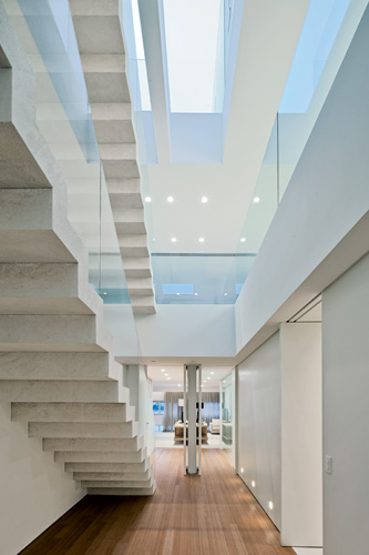 From the lowest level of the triplex's stair hall , the visitor can catch glimpses of the guest bedrooms beyond and the living area above. Skylights over the stair and a glass floor in the top s